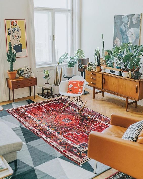 living room, wooden herringbone floor, brown leather chair, red rug, white wall, white green rug, plants, wooden cabinet
