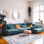 Living Room, Wooden Herringbone Floor, Teal Corner Sofa, White Wall, White Patterned Rug, Glass Window