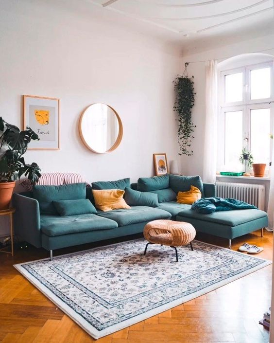 living room, wooden herringbone floor, teal corner sofa, white wall, white patterned rug, glass window