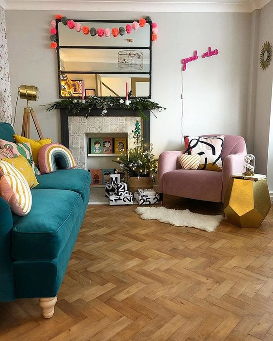 living room, wooden herringbone floor, white wall, green sofa, pink chair, mirror, fireplace