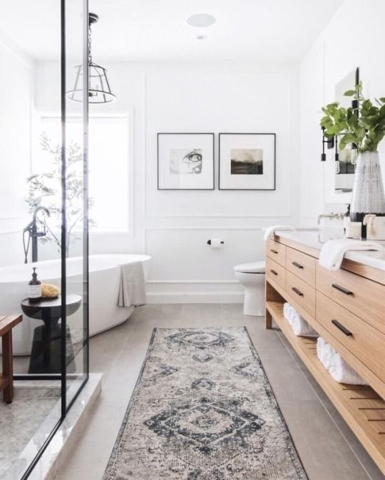 long bathroom, cream floor, white wall, white tub, light wooden cabinet, marble
