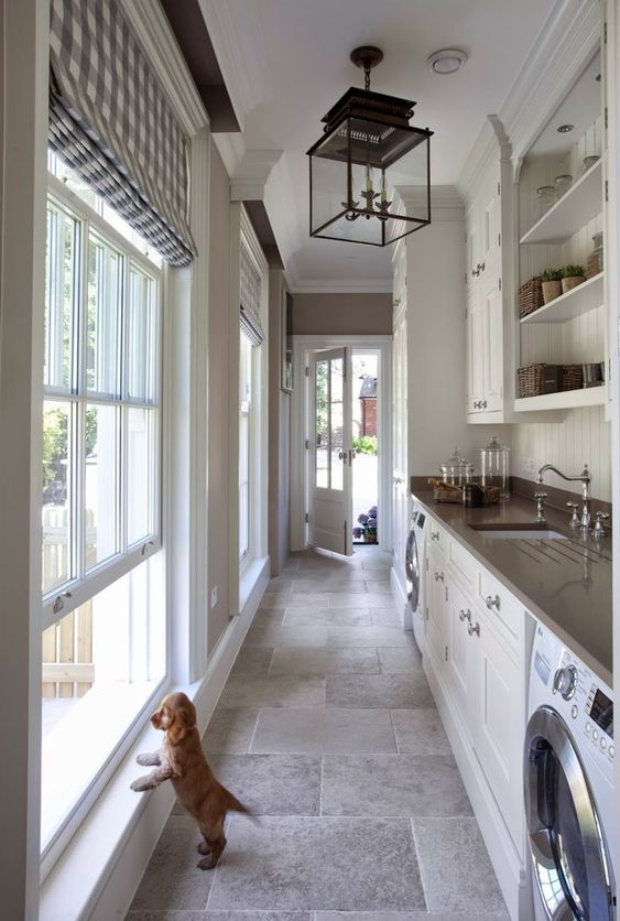 long kitchen, grey floor tiles, white wall, white bottom cabinet, silver counter top, black framed cube pendant, glass wall