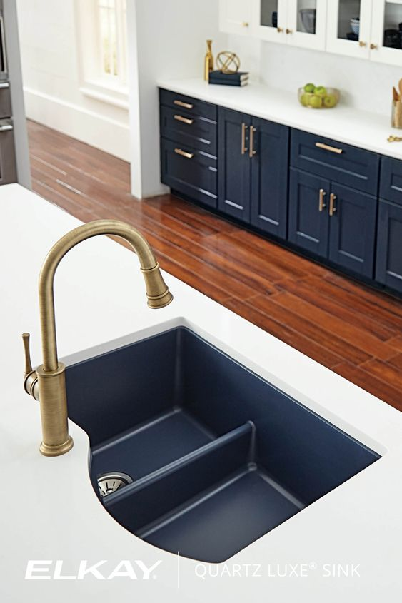 navy undermounted sink, white counter top, navy bottom cabinet, white upper cabinet, wooden floor, golden faucet