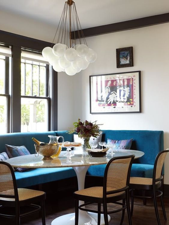 nook, blue velvety corner bench, dark wooden chairs rattan seating, white chandelier, white round table