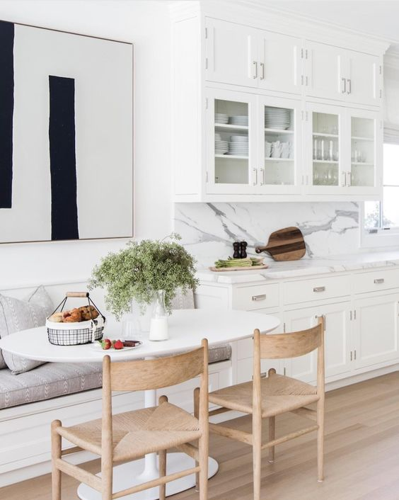 nook, wooden floor, white wall, white cabinet, white marble backsplash, white ovale table, wooden chairs, white bench, grey cushion