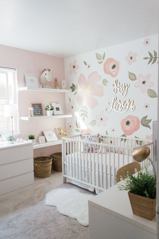 nursery, cream rug, pink wall, flowery accent wall, white crib, white cabinet, white floating shelves