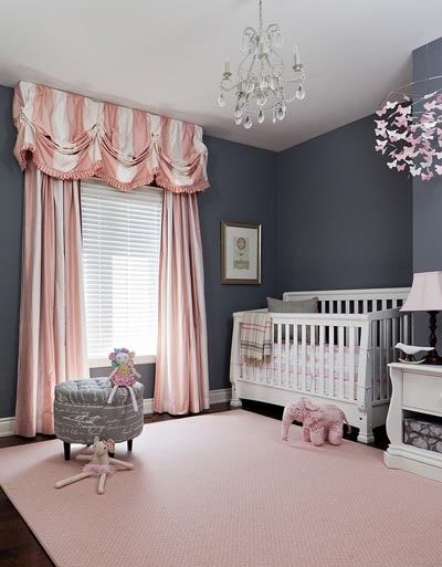 nursery, grey wall, wooden floor, pink rug, pink curtain, crystal chandelier, white table