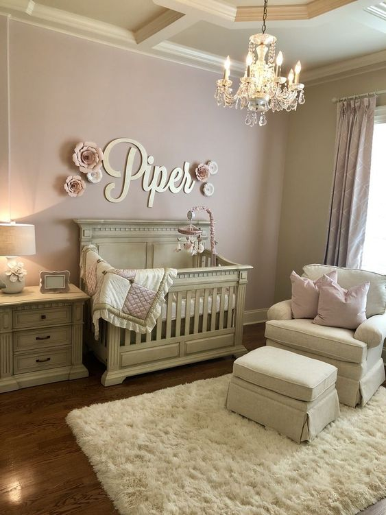 nursery, wooden floor, pink wall, cream crib, cream chair, cream ottoman, cream cabinet, crystal ottoman, white lamp