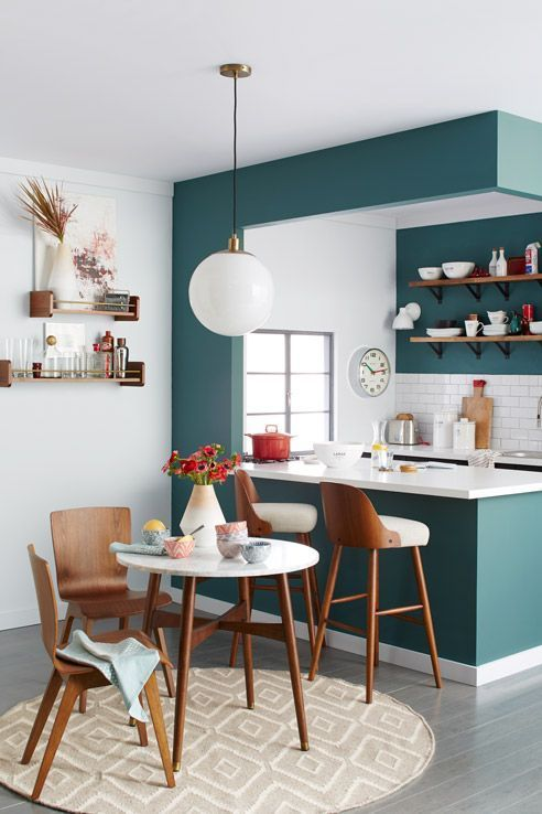 open kitchen, teal cabinet island, white counter top, white wall, white bulb pendant, wooden floor, wooden chairs, wooden stools, wooden round table
