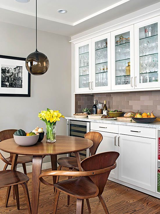 open kitchen, wooden floor, dark wooden dining set, black bulb pendant, white cabinet, brown subway backsplash