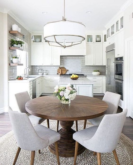 open kitchen, wooden floor, white upper cabinet, white bottom cabinet, white round pendant, floating shelves, white backsplash, round wooden table, white chairs