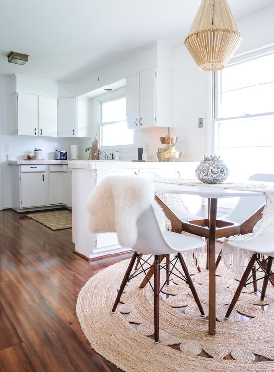 open kitchen, wooden floor, white wall, white cabinet, white round table, white midcentury modern chairs, rattan pendant, windows