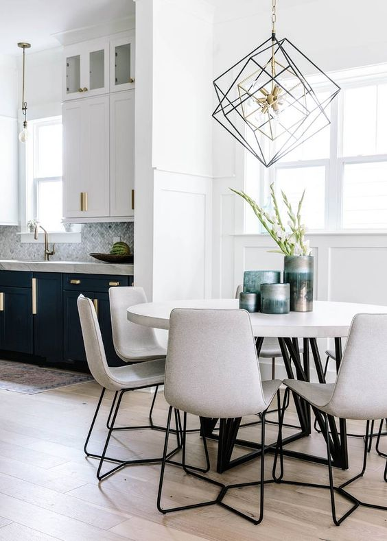 open kitchen, wooden floor, white wall, white wainscoting, whtie round dining table, white chairs, white upper cabinet, dark green bottom cabinet, pendant