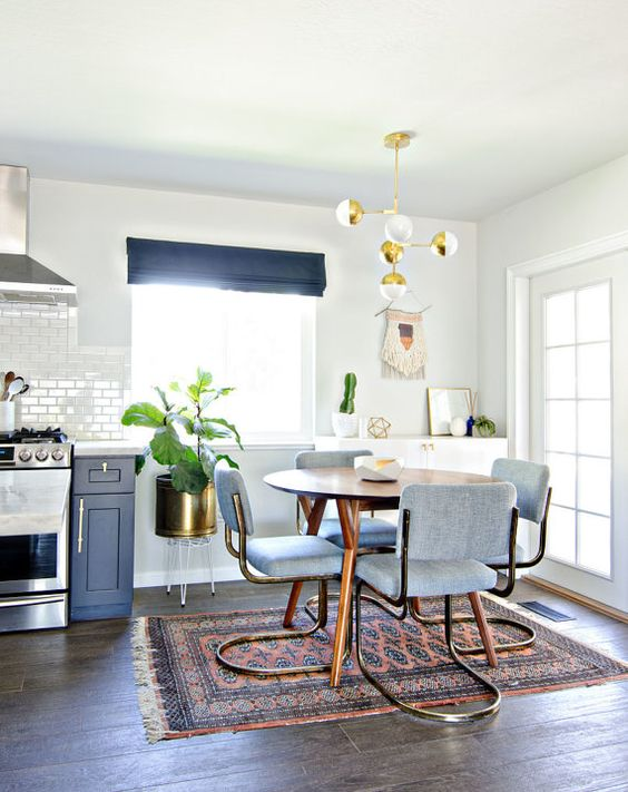 open kitchen, wooden floor, white wall, wooden round dining table, blue chairs, rug, pendant