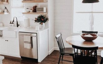 open living room, wooden floor, white wall, white planks, white bottom cabinet, white counter top, black pendant, wooden open shelves, wooden round table, dark wooden chairs
