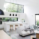 Open Room, Concrete Floor, White Wall, Black Pendants, White Kitchen, White Island, Wooden Stools, Grey Sofa, Grey Rug