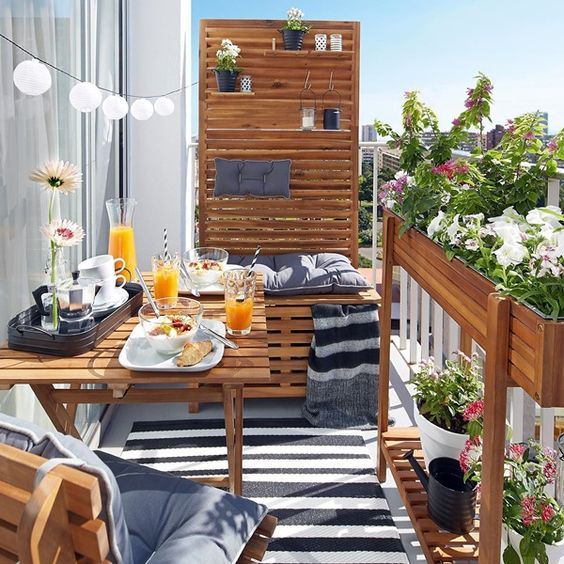 patio, grey floor, black white striped rug, wooden table, wooden chair, wooden bench with high board and shelves, wooden long pots on the fence