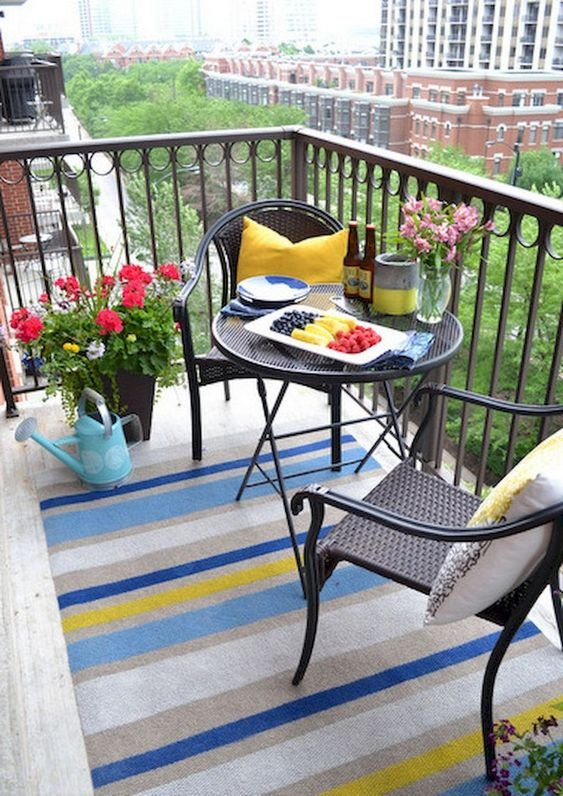 patio, white floor, colorful striped rug, black chairs, black round table, black fence