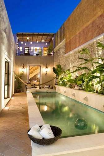pool, cream matble, brown floor, stone wall, plants along the wall