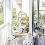 Rattan Swing In The Balcony, White Fence, White Side Table, Grey Floor