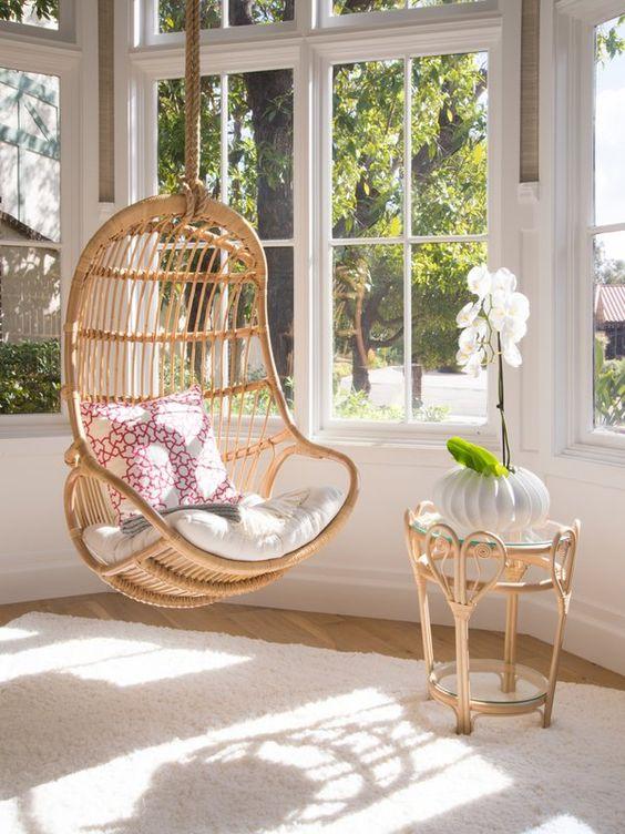 rattan swing, wooden floor, white rug, large glass window