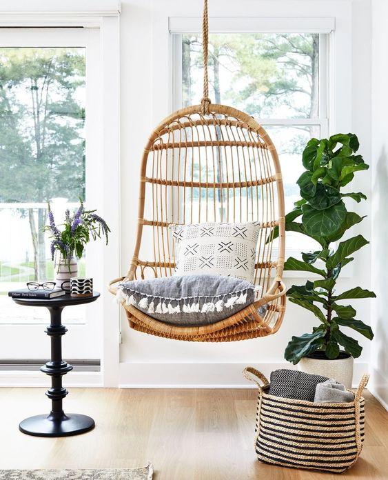 rattan swing, wooden floor, white wall, black side table, white pot