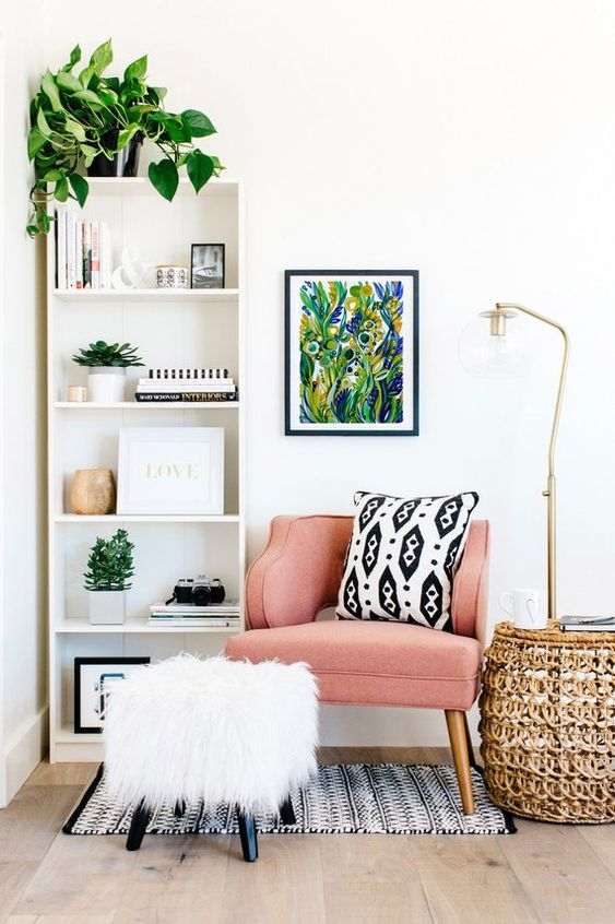 reading corner, wooden floor, white wall, white shelves, rattan table, floor lamp, pink chair, white fur ottoman