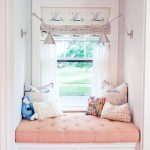 Small Alcove, Wooden Floor, White Wall, White Framed Window, White Built In Bench With Drawers, Orange Tufted Cushion