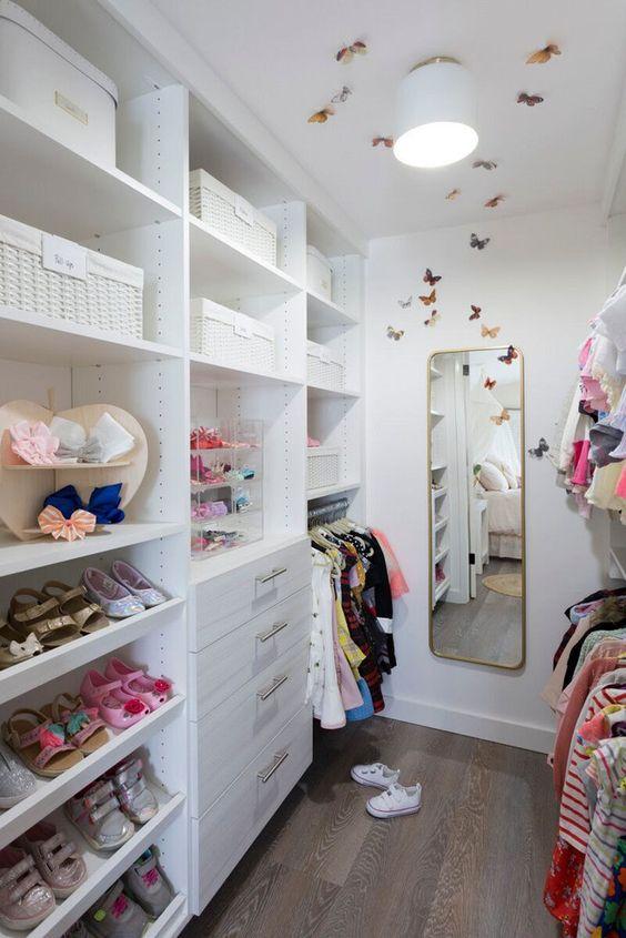 small closet, white cabinet, white shelves, mirror, long rack
