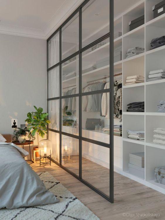 small closet, wooden floor, white shelves, rod, glass partition, white rug, white bedding