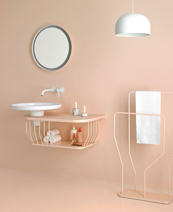 soft peach wall and floor, peach floating vanity, white round sink, white pendant, peach metal line rack