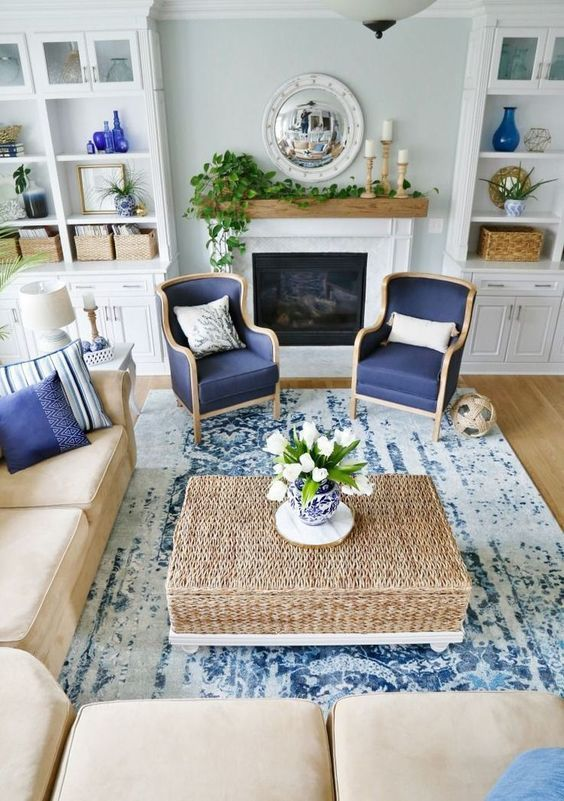 traditional living room, wooden floor, blue rug, cream corner sofa, blue chairs, rattan coffee table, white built in shelves, white fireplace