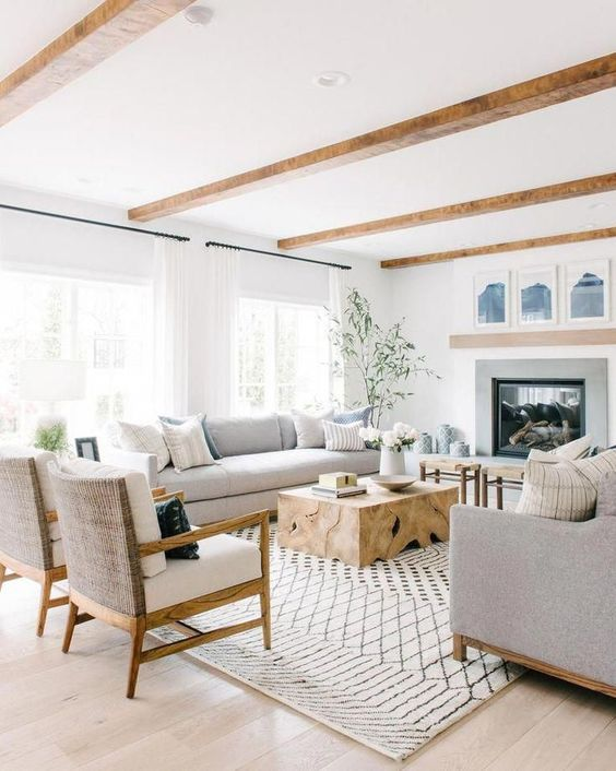 traditional living room, wooden floor, white wall, fireplace, grey sofa and chairs, wooden coffee tbale, wooden chairs with white cushions, wooden beams