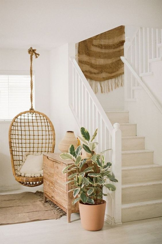 under the stairs, white fence, brown floor, brown wooden cabinet, rattan swing