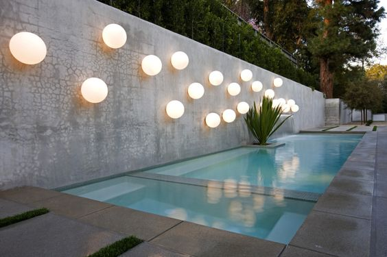 white ball wall fixture, concrete floor, concrete wall, plan along the wall