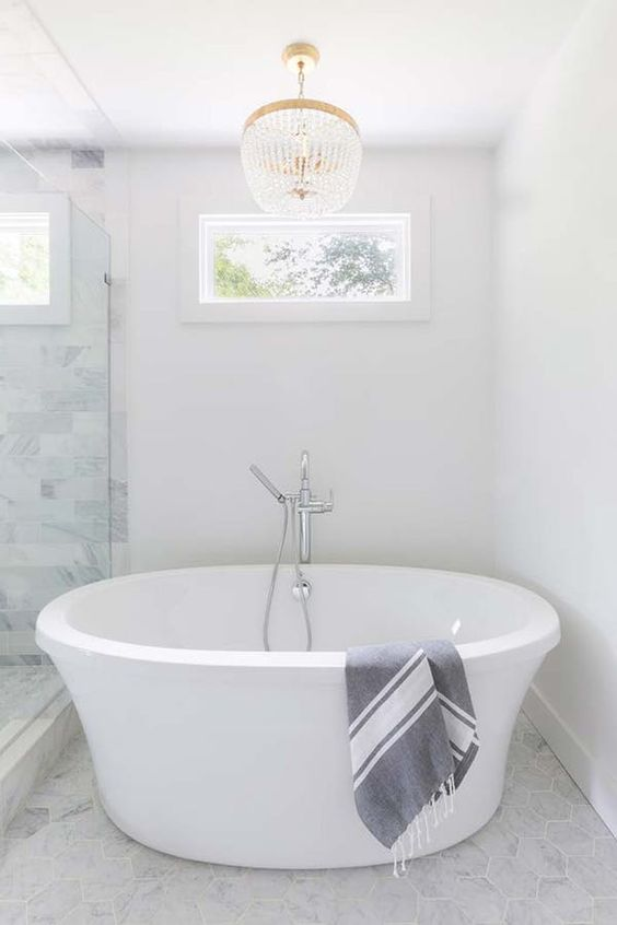 white large bowl tub, white marble floor, white marble wall, white wall, crystal chandelier