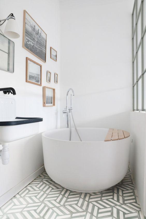 white round soaking tub, geometrical floor tiles, white wall, white farmhouse sink with black lines, white sconce