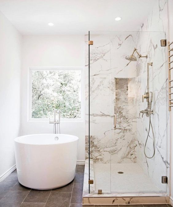 white round soaking tub, white wall, marble shower wall, grey floor tiles, metal faucet
