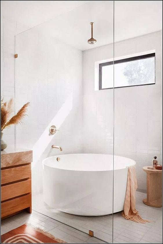 white round soaking tub, white wall tiles, white floor tiles, wooden cabinet, golden faucet