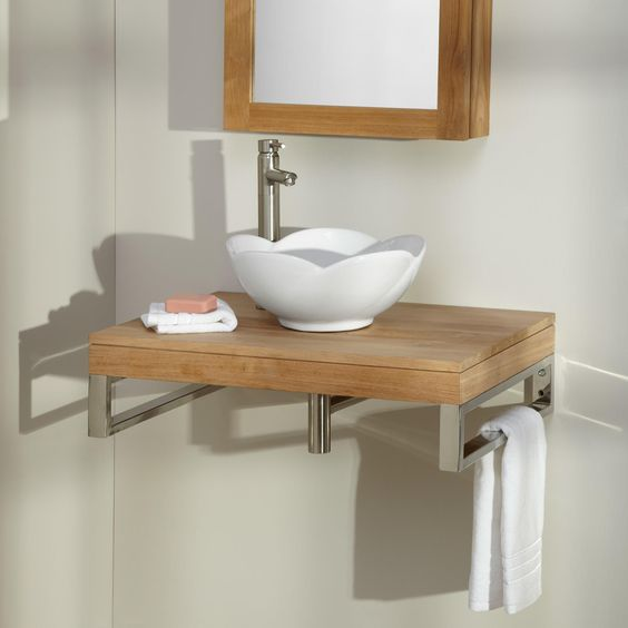 white sink with curves on top, wooden floating vanity, cream wall, wooden framed mirror