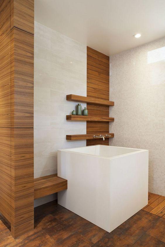 white square soaking tub, wooden floor, white wall, wooden shelves, cream marble wall tiles