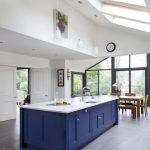 White Vaulted Ceiling, Glass Ceiling Windows, White Pendants, Blue Island With White Counter, Grey Floor