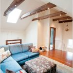 White Vaulted Ceiling, Wooden Horizontal Beams, Blue Sofa, Brown Ottoman, Blue Rug, Wooden Floor, Pendants