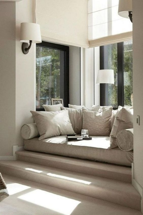 window bed, cream stairs, white wall, white sconces, grey cushion, grey pillows