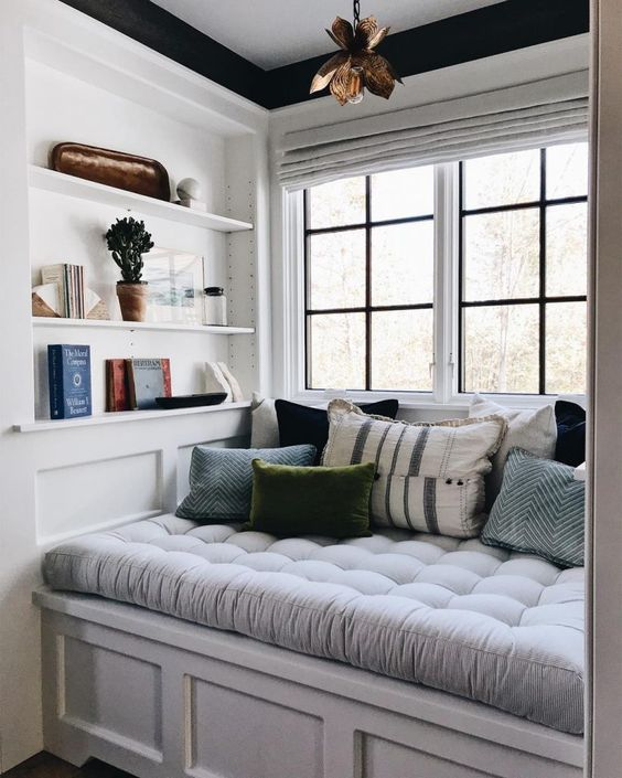 window bed, white tufted cushion, white bench, white built in shelves, glass windows, golden pendant
