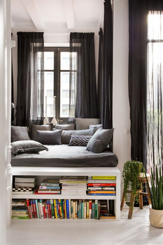 window, white wooden floor, white wall, white shelves, grey cushion, grey pillows, dark grey cushion
