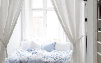 window, wooden floor, white wall, white wooden built in shelves, white bed, white cushion, blue converter
