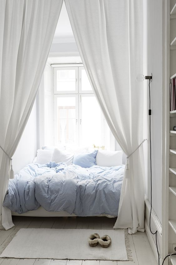 window, wooden floor, white wall, white wooden built in shelves, white bed, white cushion, blue converter
