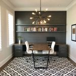 Working Space, Wooden Floor, Patterned White Black Rug, Black Wooden Accent Wall, Black Floating Shelves, Dark Cabinet, Dark Table, White Wall, White Chairs, Chandelier