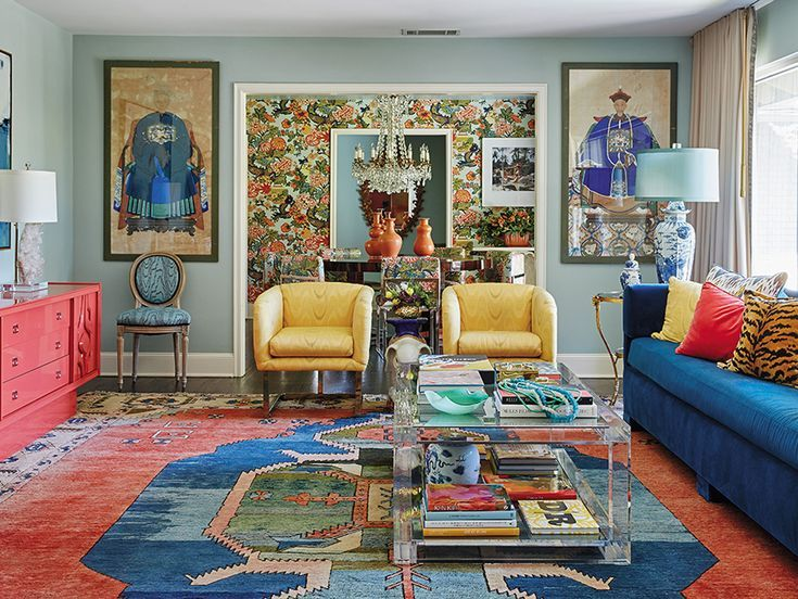 living room, patterned rug, blue wall, blue sofa, yellow chairs, orange cabinet, chinese paintings, blue white chine on table lamp, chandelier